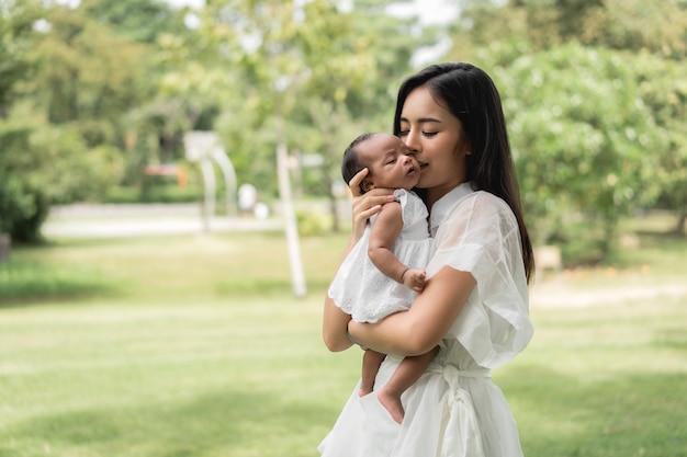 갓난아기를 안고 있는 아시아의 아름다운 어머니는 자고 사랑을 느끼며 부드럽게 만지고 공원의 푸른 잔디에 앉아 있다