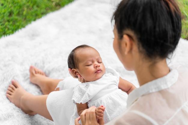 彼女の新生児を保持しているアジアの若い美しい母親は眠っていて、愛を感じています