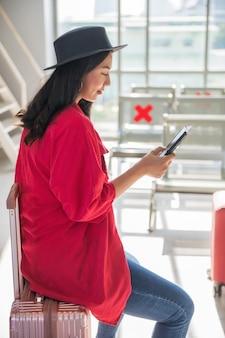 아시아의 젊고 아름다운 여성은 수화물 가방에 앉아 스마트폰을 사용하여 채팅하고, 문자를 보내고, 소셜 미디어를 즐깁니다. 그녀는 공항 터미널에서 출발을 기다립니다. 휴일 휴가 및 여행 개념입니다.