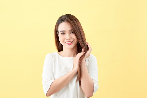 笑顔と滑らかな彼女の髪、自然なメイク、美しさの顔、青い背景で隔離のアジアの若い美しい女性。