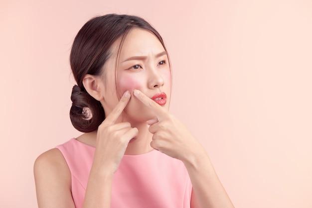 アジアの若い美しい女性が、にきびを絞って取り除く。