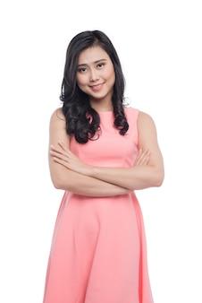 Азиатская молодая красивая женщина с длинными черными волосами в розовом платье, стоящем над белизной.