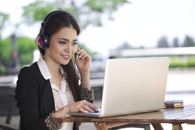 コーヒーショップでラップトップに取り組んでいるアジアの若い美しい女性