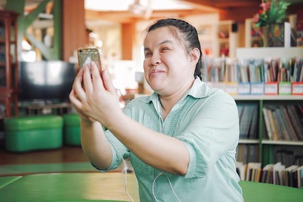 創造的な職場でスマートフォンを使用してselfieまたはビデオ通話を取っているアジアの若い盲目の女性障害者