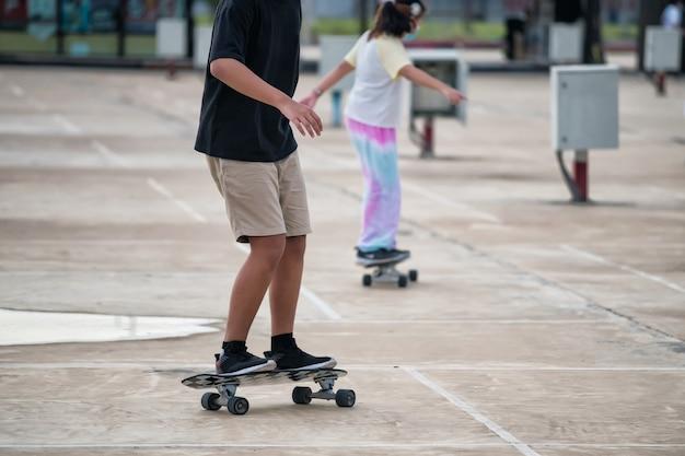 아시아의 어린 소년과 소녀 서퍼는 여름에 도시 거리 배경에서 서핑보드나 서핑 스케이트로 즐거운 시간을 보냅니다. 보디 빌딩과 건강한 라이프 스타일. 익스트림 스포츠의 새로운 트렌드.