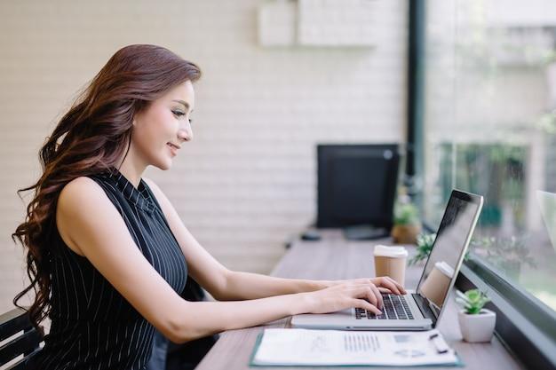 아시아 젊은 비즈니스 소녀는 커피숍 카페에서 노트북 작업을 하며 휴식을 취합니다.