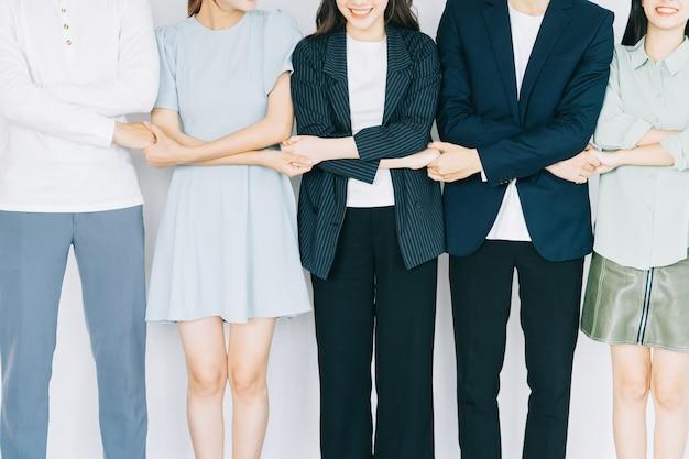 アジアの若いビジネスマンは連帯を示すために手をつないでいます