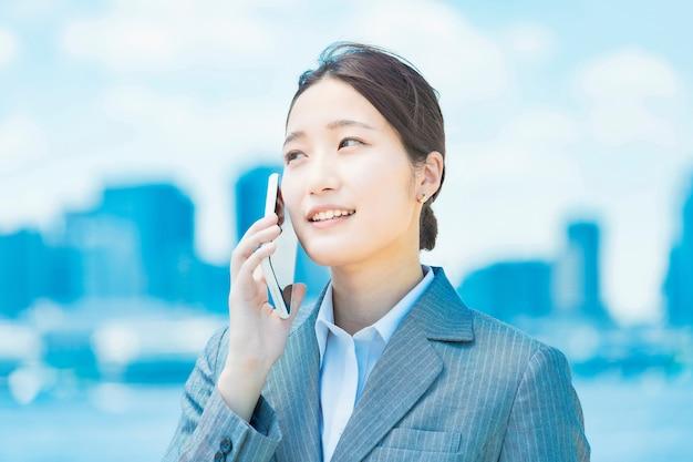 スマートフォンで呼び出すアジアの若いビジネス女性