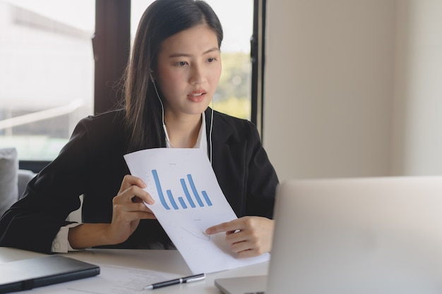 ノートパソコンを介して事務処理とビデオ通話を保持しているアジアの若いビジネス女性