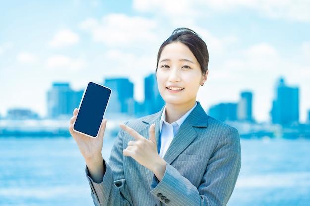 Азиатская молодая деловая женщина, работающая со смартфоном