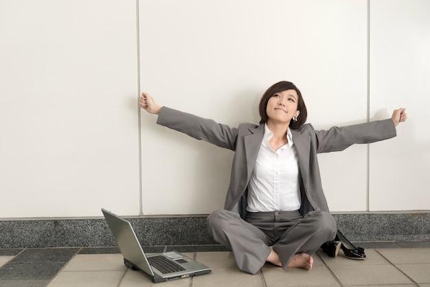 アジアの若いビジネスウーマンは靴を脱いで、モダンな建物の地面に座ってリラックスします。