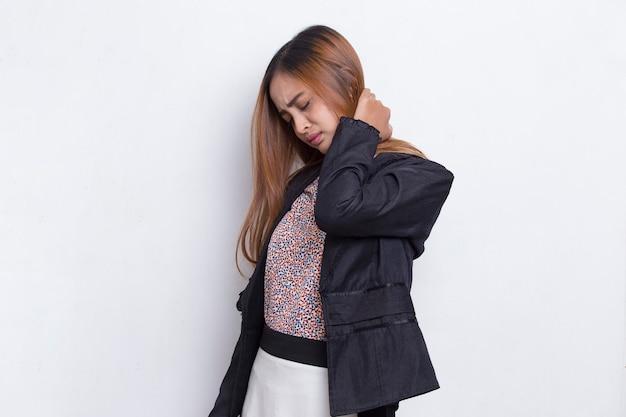喉の痛みと白い背景で隔離の肩の痛みを持つアジアの若いビジネス女性