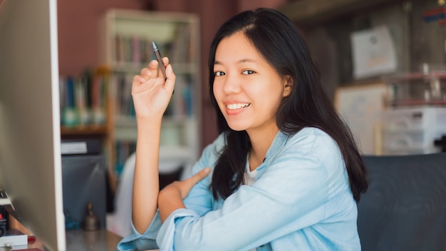Asian young business woman working from home office.