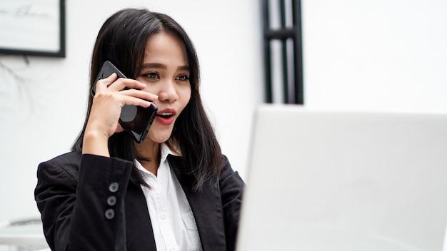 아시아 젊은 비즈니스 여자 컴퓨터에서 작업하고 사무실에서 스마트 폰 이야기