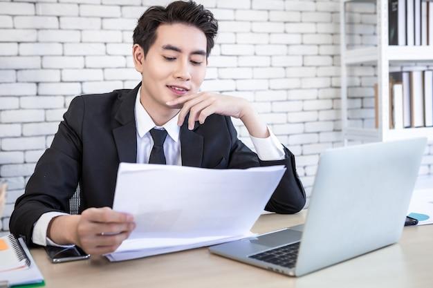 아시아의 젊은 사업가는 사무실 배경에서 사업 손실 후 목탁에 있는 문서 사업 계획과 노트북 컴퓨터를 보도록 강조했습니다.