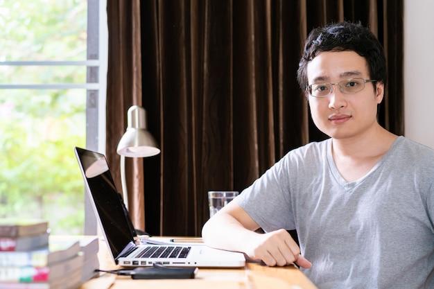 Азиатский молодой бизнесмен в обеспокоенных эмоциях, стрессе от трудолюбивой и нездоровой жизни. азиатский молодой взрослый, работающий дома в течение периода карантина, вызывает пандемию covid-19 или coronavirus 2019.