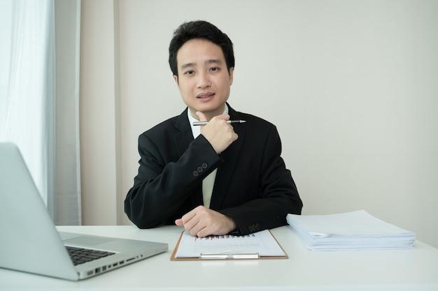 Молодой азиатский бизнесмен проводит онлайн-видеоконференцию, работая дома из-за коронавируса или пандемии covid-19. азиатский бизнесмен, используя ноутбук для онлайн-встречи.