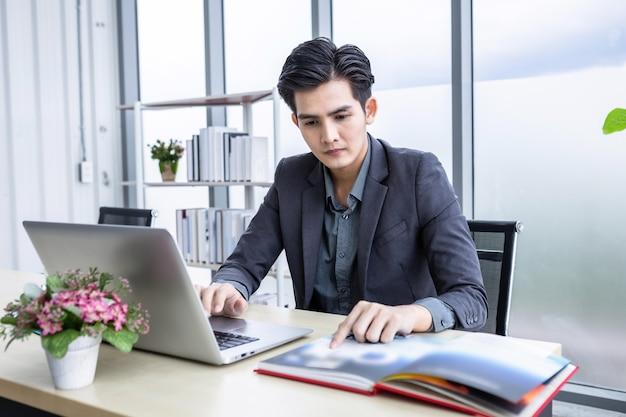 アジアの青年実業家はラップトップコンピューターで成功したビジネスプランを見る