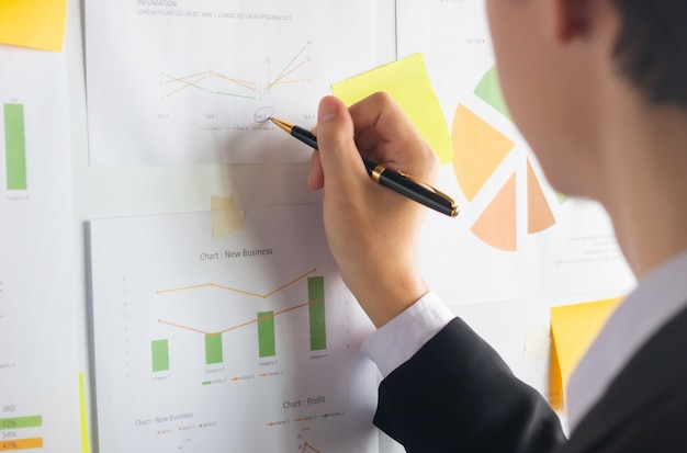 Asian young businessman using pen work analyzing financial documents on whiteboard
