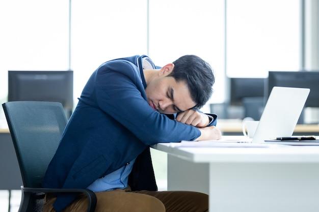アジアの青年実業家は遅くまで働き、事務室のバックグラウンドでラップトップコンピューターで眠りに落ちました。
