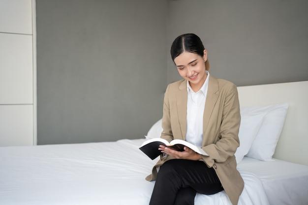 ベッドに座っているアジアの若い実業家は、出張中にホテルの寝室で本を読む