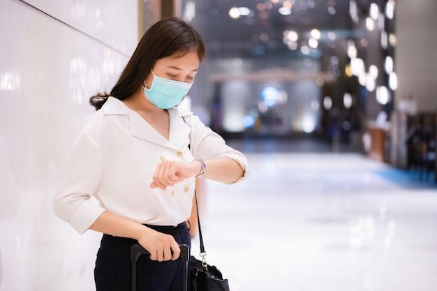 Азиатская молодая бизнесвумен гуляет и смотрит на часы в отеле, женщина в случайном умном бизнесе ждет кого-то в вестибюле отеля и смотрит на часы. деловые поездки и концепция отпуска.