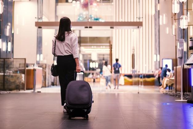 Азиатская молодая бизнесвумен гуляет и смотрит на смартфон в отеле, женщина в случайном умном бизнесе несет чемодан - багаж в вестибюле отеля.