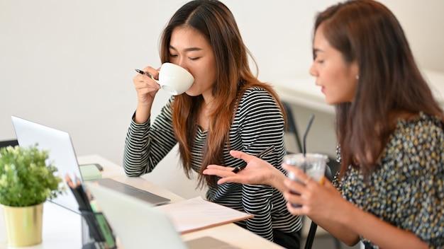 Азиатские молодые бизнесмены работают с портативным компьютером и пьют кофе в коворкинге в кафе