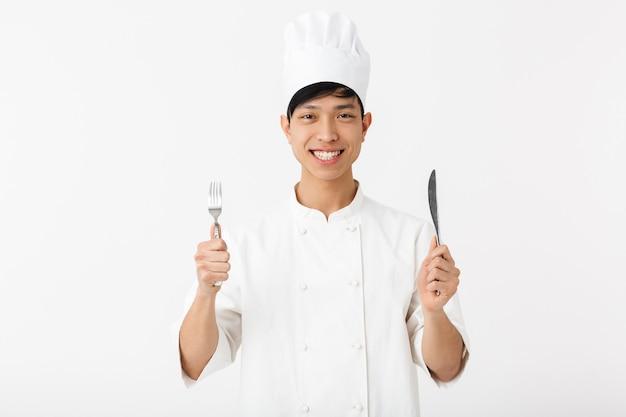Азиатский молодой главный мужчина в белой форме повара улыбается в камеру, держа в руках столовые приборы, изолированные на белой стене