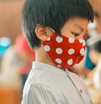アジアの幼児は、コロナウイルスcovid-19に対する保護のために赤いマスクを着用しています