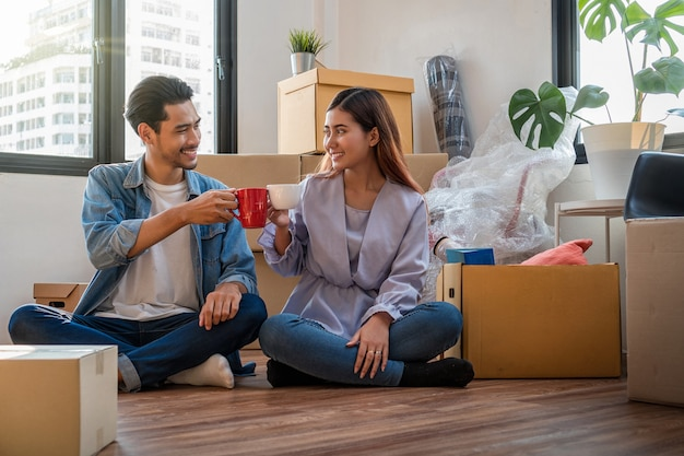 Asian young couple are clinking coffee cups after successful packing the big cardboard boxes