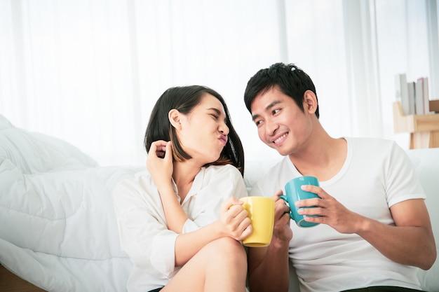 朝の悪い部屋、レジャー、カップル、関係、バレンタインの概念でコーヒーと一緒に楽しんでいるアジアの若いカップル。コピースペースのある写真 Premium写真