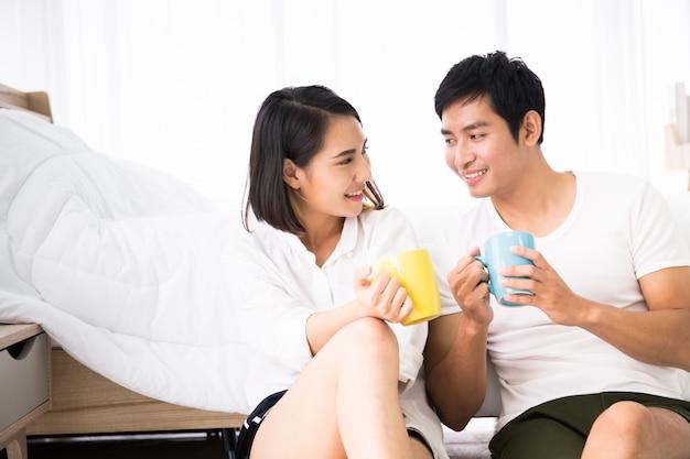 朝のコーヒーと一緒に楽しむアジアの若いカップル