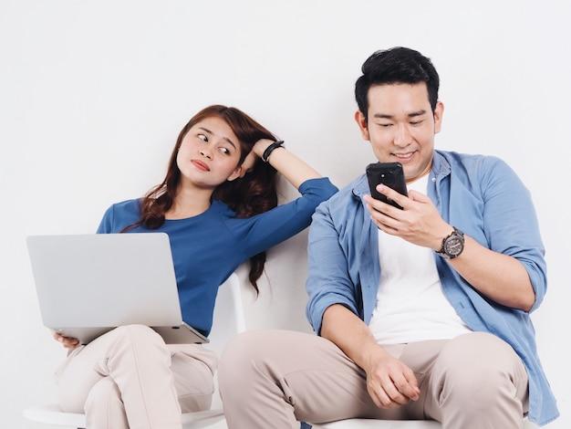 Азиатский молодой любовник пар воюя для умного телефона в живущей комнате дома.