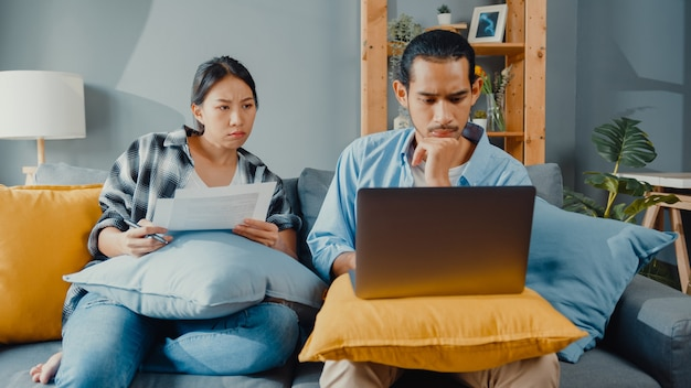 Asian young couple man and woman sit on couch with laptop check documents