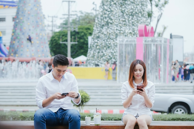 Asian young couple play phone happily uninterested in each other