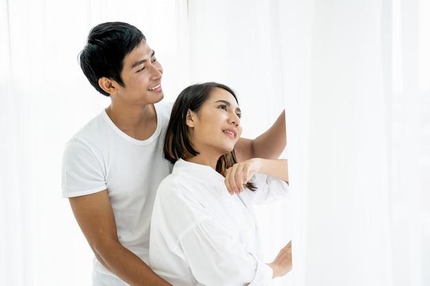 Азиатская молодая пара портрет, пара стоя и говорить у окна в первой половине дня.