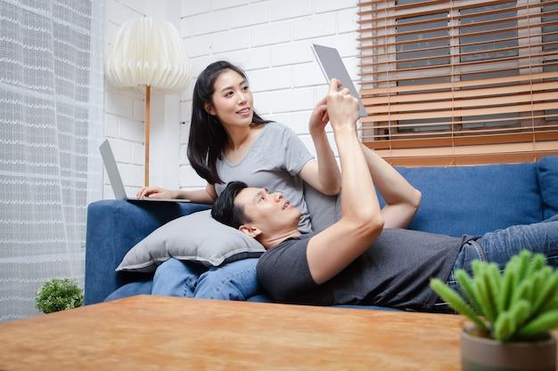 아시아 젊은 부부는 휴가 기간 동안 집에서 파란색 소파에 앉아 휴식을 취합니다.