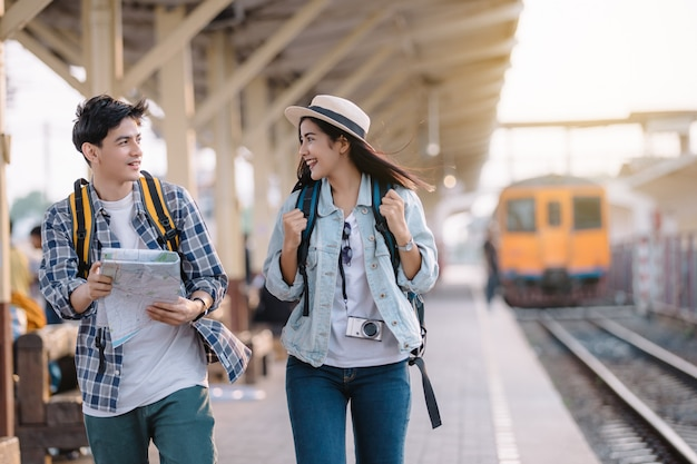 Asian young couple of travellers holding map in hands vintage style