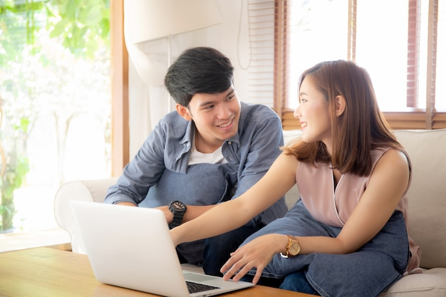 Asian young couple using laptop computer think and searching internet together