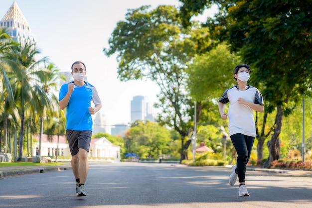 아시아 젊은 부부 여자와 남자는 조깅 및 도시 공원에서 야외 excyinging 및 방콕, 태국에서 covid-19 전염병 동안 맞는 체재를 위해 얼굴에 보호 마스크를 착용.