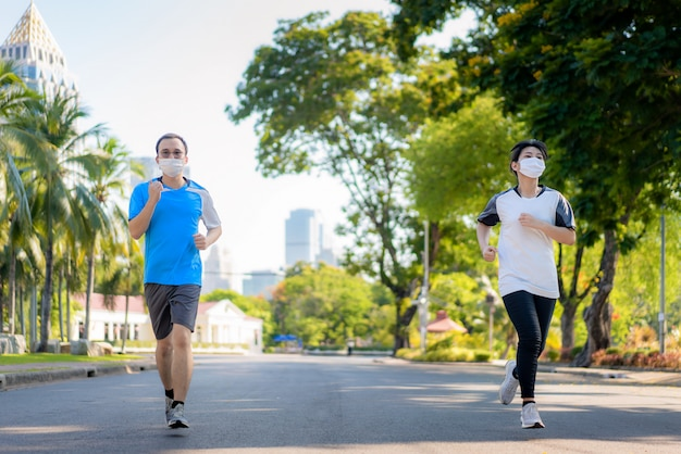 Asian young couple woman and man are jogging and exciseing outdoor in city park and wearing protective mask on face for stay in fit during covid-19 pandemic in bangkok, thailand.