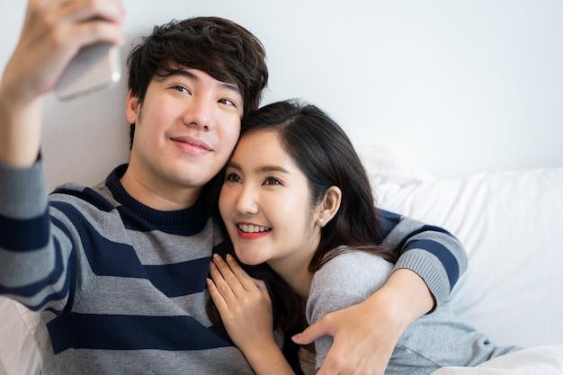 아시아 젊은 커플 남자와 여자 침실에서 뒤에서 남자 친구를 포옹 하는 여자