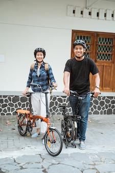 外出前にアジアの若いカップルが折りたたみ自転車を準備し、ヘルメットを着用