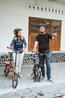 Азиатские молодые пары готовят складные велосипеды и надевают шлемы перед выходом на улицу