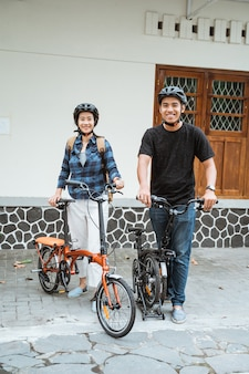 Asian young couples prepare folding bikes and wear helmets before going out