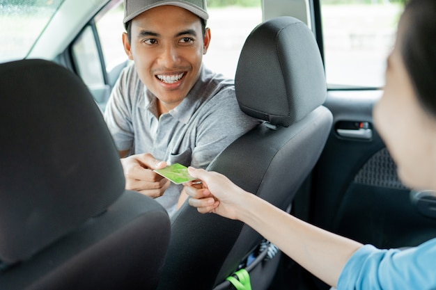 Asian young drivers kindly approve payment by credit card