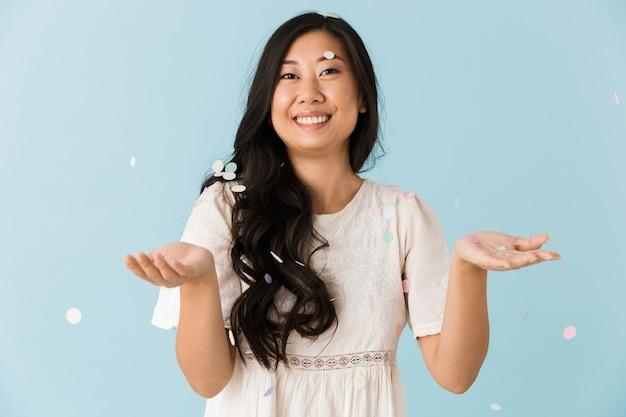 Азиатская молодая эмоциональная женщина изолирована над синей стеной над конфетти