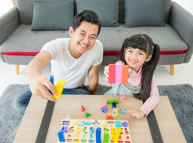 Asian young father and daughter indoors sit on floor playing with toy and smiling