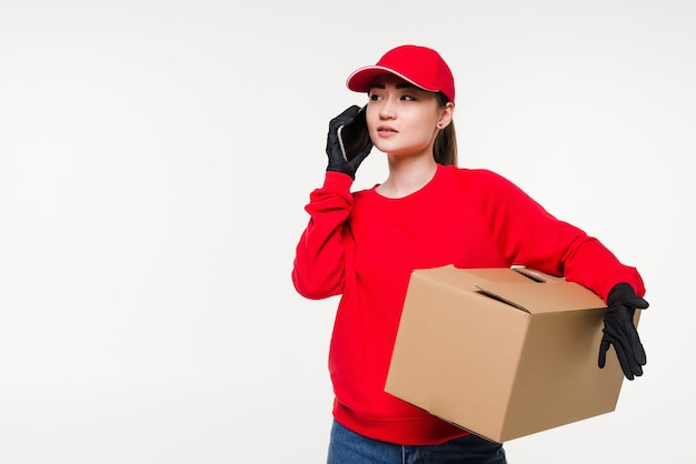 Asian young female delivery worker standing in white wall using mobile smartphone talking with customer checking shipping address